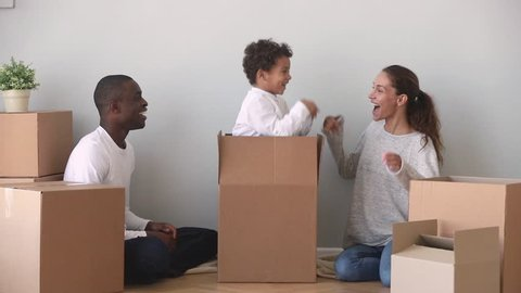Happy mixed ethnicity family having fun unpacking boxes on moving day, cute kid child son jump out of box make surprise to african american dad and caucasian mom laughing enjoy relocation in new home