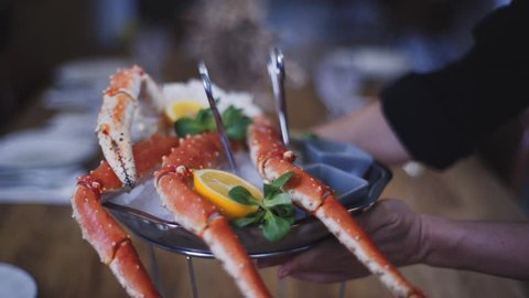 Crab lies on ice in a dish with lemon and basil. Beautiful crab feed on ice. A dish of crab stands on a wooden table in a restaurant.