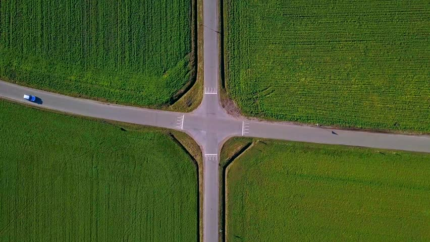Bird eye view of a perfect symmetrical crossroad with green fields and 2 cars passing   Shutterstock HD Video #1027580213