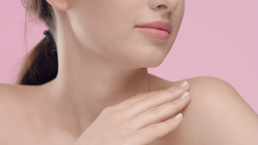 Close-up beauty portrait of young Caucasian woman with smooth and healthy skin strokes her skin at collarbone area against light pink background | Skincare concept | Shutterstock HD Video #1027606283