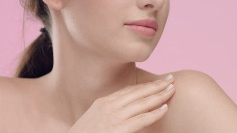 Close-up beauty portrait of young Caucasian woman with smooth and healthy skin strokes her skin at collarbone area against light pink background | Skincare concept