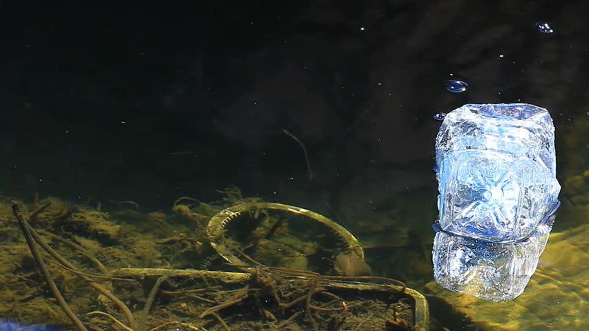Empty plastic bottle in lake | Shutterstock HD Video #1027626053