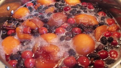 Cooking stewed fruit. Cooking at home.  Boiling fruit compote. Pan with compote of fresh berries on stove. Stir the boiling compote.