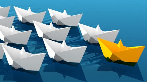 Leadership concept, yellow leader boat with white paper boats floating in the blue waves of the sea