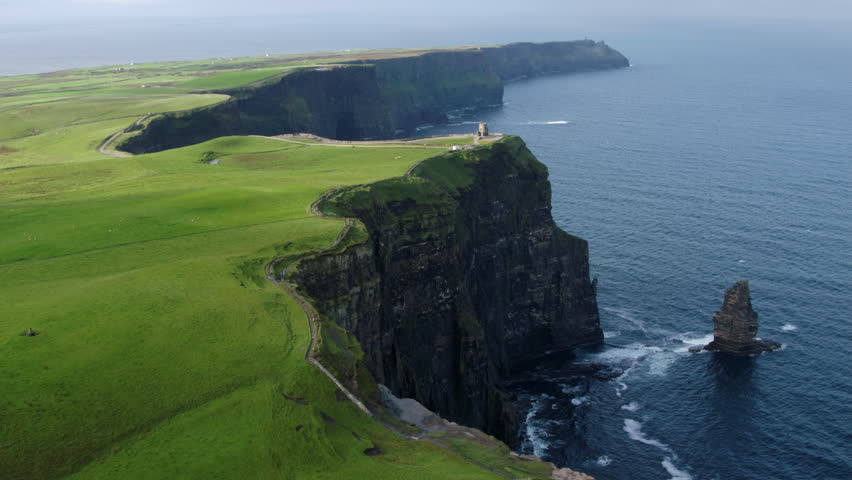 Aerial drone footage in 4k of the Cliffs of Moher in Ireland. Shot at 60fps, features a static shot of O'Brien's tower. | Shutterstock HD Video #1027640033