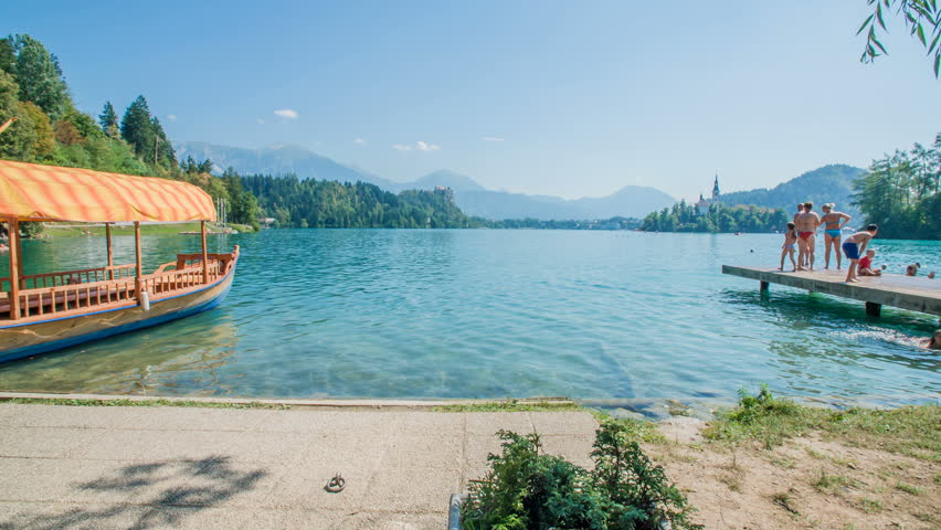 BLED, SLOVENIA - 20. SEPTEMBER 2018 People are standing on a pier by the Lake Bled and some of them jump into the water. The Pletna boat is anchored to the shore. #1027692683