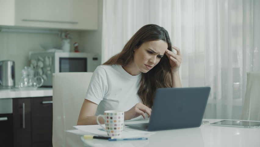 Sad woman working laptop computer at kitchen. Unhappy person use computer technology at home. Worried girl stress at freelance work at home workplace. Upset woman looking at laptop screen | Shutterstock HD Video #1027710653