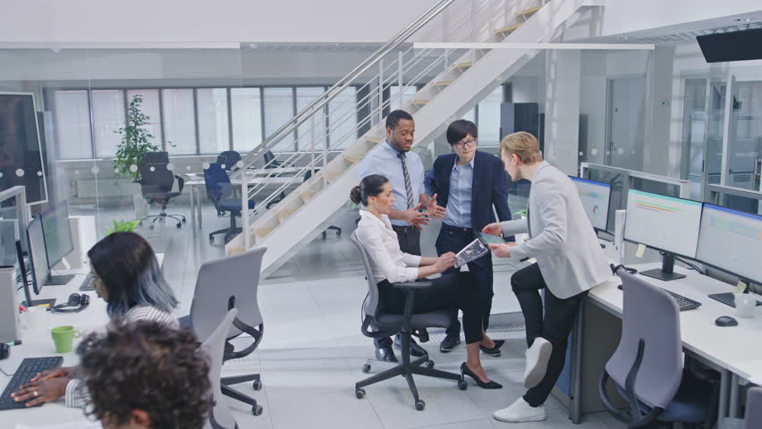 Diverse Multinational Team of Business Managers and Specialists Chat and Discuss Graphs on Paper and Tablet Computer. Young and Motivated Business People in Modern Open Office. | Shutterstock HD Video #1027712513