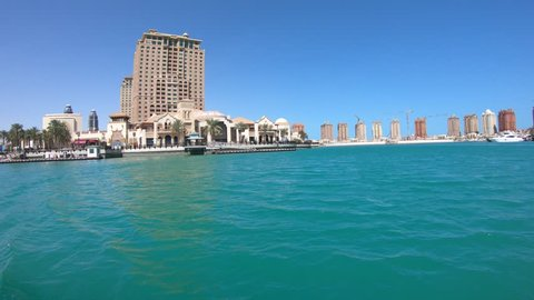 Sea view of Doha West Bay skyline with luxurious resort hotels with blue sky in Porto Arabia, The Pearl-Qatar's main harbor in Doha city, Persian Gulf, Middle East.