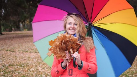 Happy longhaired blonde woman with a large colourful spinning umbrella in a red coat in the autumn park turns around and smiles at the camera with yellow maple leaves in her hand.