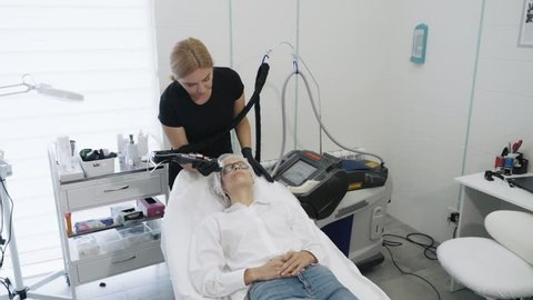 Slow motion cosmetologist with special equipment does laser procedure for removal of blood vessels on girl's face. Beautician makes laser treatment on young woman face. Concept medical clinic