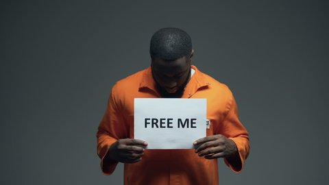African-american prisoner holding Free me sign in cell, innocent asking for help