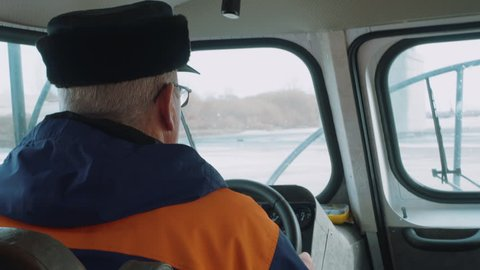 Driver man holding steering wheel hovercraft boat while driving on winter river. Senior man riding on hovercraft on icy lake back view