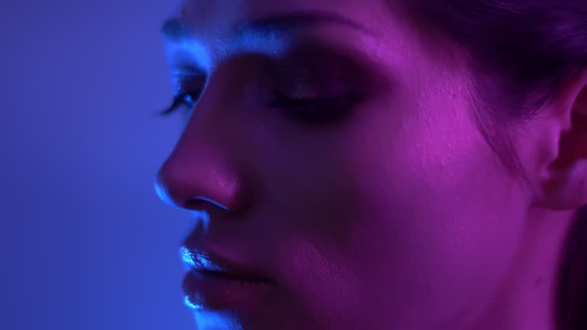 Bright fashion model in colorful purple and blue neon lights moving slowly and watching into camera in studio. #1027754663