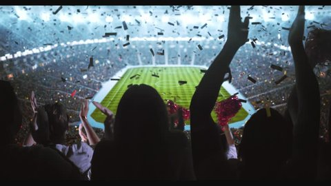 Group of cheering fans watch a sport championship on stadium. Their team wins and everybody are celebrating this event. People are dressed in casual clothes. Colorful confetti fly in the air.