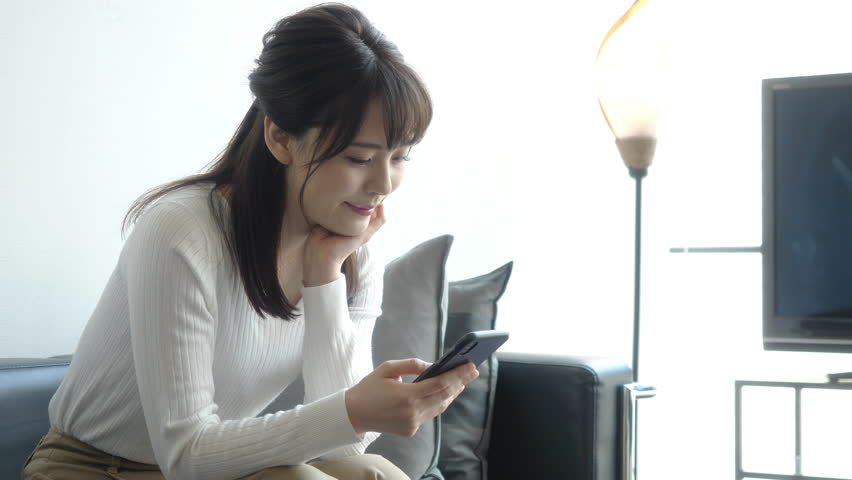 Attractive asian woman using a smart phone in living room. | Shutterstock HD Video #1027764503