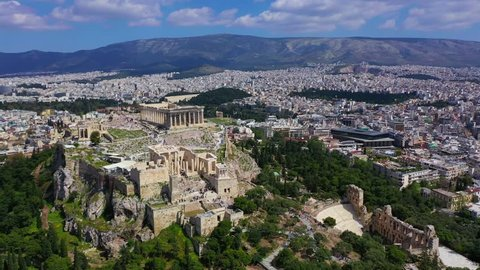Aerial birds eye view video of iconic Acropolis hill, Propylaia entrance, the Parthenon and Odeon of Herodes Atticus, Athens historic centre, Attica, Greece
