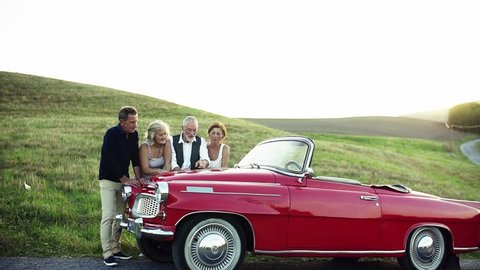 Two senior couples standing by cabriolet on a road trip in summer, planning.