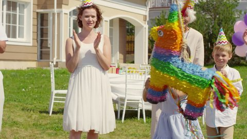 Happy multigenerational family in party hats clapping hands and smiling while watching little girl striking piñata with bat at birthday celebration outdoors on summer day