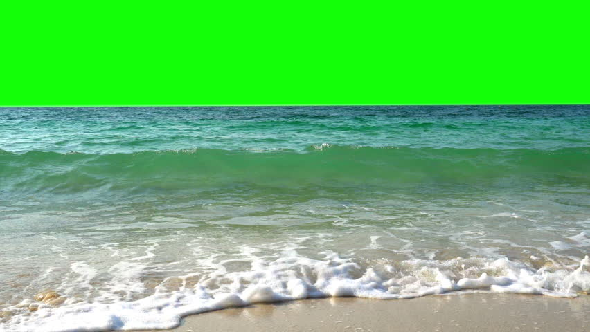 4K Video Landscape wide shot of blue sea water waves splashing against tropical sand beach in the island with chroma key green screen background. The sun glimmering flares peeking the sea surface.