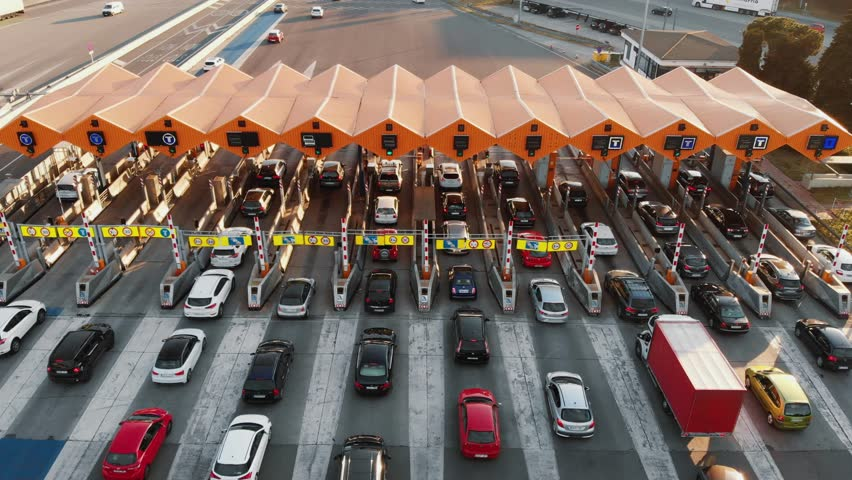 Barcelona / Spain 14 04 2019: Aerial, drone still backward footage of an overloaded toll road or tollway on the controlled-access highway at the sunset. Forced traffic jam concept. #1027813403