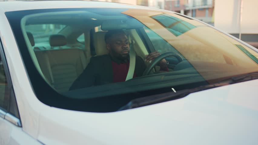 Happy young handsome african american man sitting behind the wheel of the car goes stylish vehicle arm auto street automobile businessman buy jacket close up slow motion