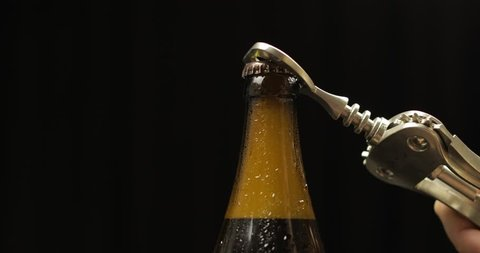 Opening cold bottle of beer with bottle opener. Cold beer on a black background. Craft light beer in bottle with condensate and water drops. Close-up shot
