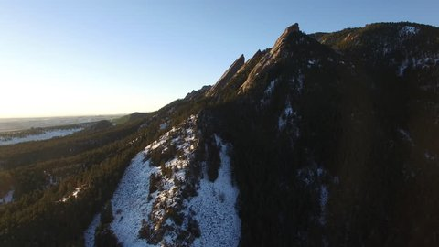 Aerial: Tree Covered Mountains And Valley with Snow In Evening Sun in Boulder, Colorado