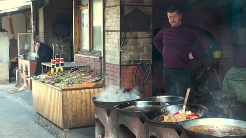 Yalta, Russia, October 12, 2014: Male Tatar stands in front of vats and prepares on fire dishes of Tatar cuisine. In background is table with meat strung on skewers and man lifts lid of saucepan..