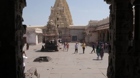 Hampi, india- 28 feb 2019: virupaksha temple, the oldest shrine in unesco  world heritage group of monuments and remains an active hindu worship site-  the head priest walking around being followed