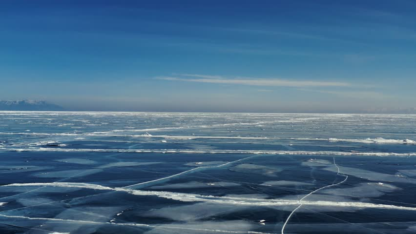 Aerial Perspective View of Beautiful Deep Blue Ice Textured Frozen Baikal Lake Surface from above Captured with a Drone at Sunny Winter Day in Russia