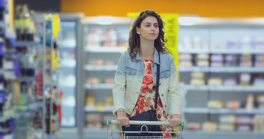 Pretty young woman walks through the supermarket hall with a cart and smiles. Girl chooses goods in the store and carries a trolley. | Shutterstock HD Video #1028002073