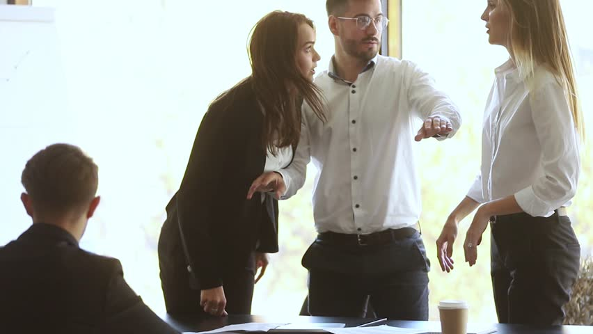Male colleague set apart angry business women coworkers argue about mistake in papers fight at corporate office meeting, mad female employees clients quarreling shouting conflict at workplace concept | Shutterstock HD Video #1028009543