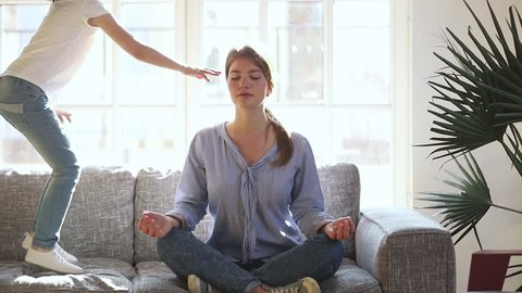 Mindful single mother meditating sitting on sofa while active energetic child daughter jumping playing, calm young mom doing yoga exercise at home for stress relief relaxing with naughty little kid