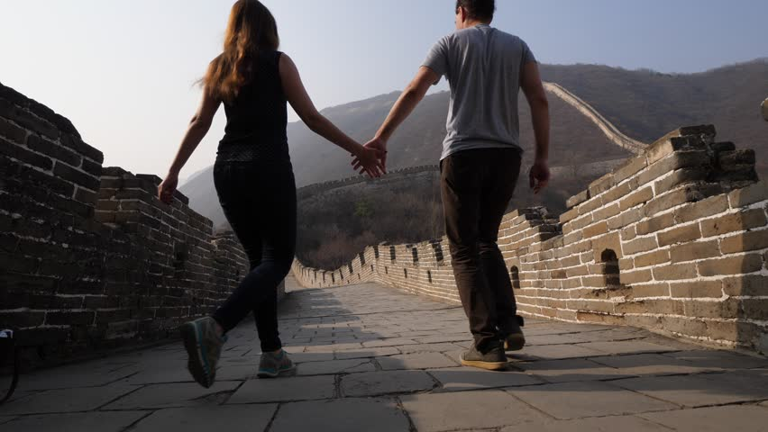 Young woman and man join hands and go along Great Wall of China. Low camera, wide angle shot from floor of stone paved walkway. Tourist pair explore famous Chinese landmark, Mutianyu section