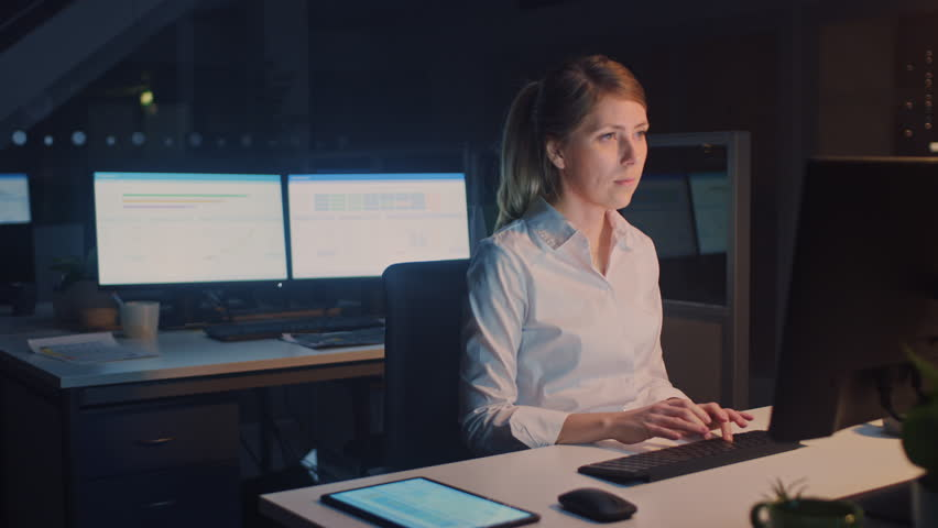 Following Shot of Businesswoman Walking into Corporate Office with Digital Tablet Computer, She Takes Her Place at Desktop Computer and Proceeds Working on Important Project | Shutterstock HD Video #1028084273
