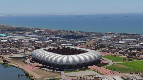 Port Elizabeth, South Africa - circa 2010s: Aerial orbit around Nelson Mandela Bay Stadium. Wide view of stadium in context of industrial area, situated next to North End Lake