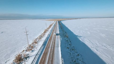 AERIAL: 4K drone aerial of frozen Lake Winnipeg in Manitoba, Canada and Grassy Narrows Marsh near Hecla, Gull Harbour, and Riverton. Onlooking the reed-filled marsh is the snowy, icy, cold lake.