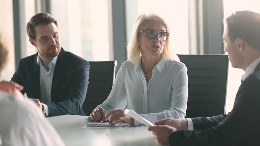 Mature old female company leader negotiator handshake male business partner or client make work deal formal agreement shake hands sitting at negotiation table express gratitude at team office meeting | Shutterstock HD Video #1028099093