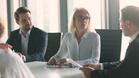 Mature old female company leader negotiator handshake male business partner or client make work deal formal agreement shake hands sitting at negotiation table express gratitude at team office meeting