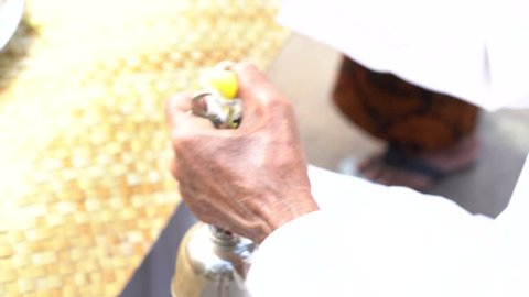 The hands with bell of the priest during the religious ceremony on central street in Ubud, Island Bali, Indonesia . Close up