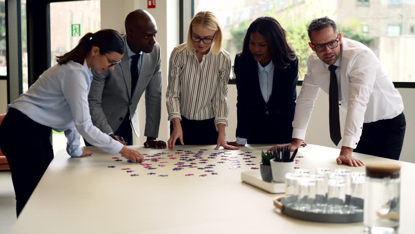 Smiling group of diverse businesspeople trying to solve a large jigsaw puzzle while standing together around a boardroom table | Shutterstock HD Video #1028171303
