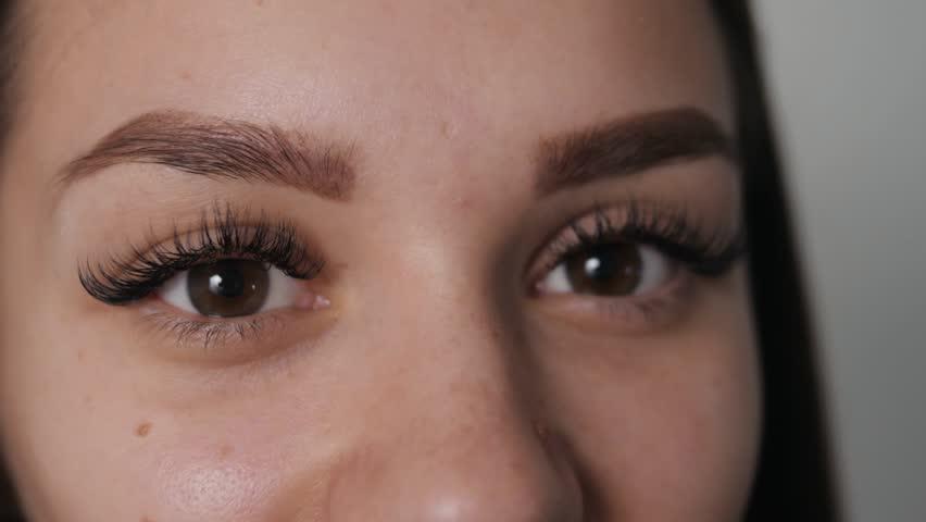 Beautiful Fashion Luxury Makeup, hyaluronic acid long eyelashes, perfect skin facial make-up. Beauty Brunette model woman holiday make up close up. Eyelash extensions, big lips false eyelashes smiling | Shutterstock HD Video #1028196983