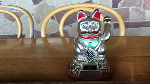 Asian figurine lucky charm talisman cat on a wooden restaurant table.