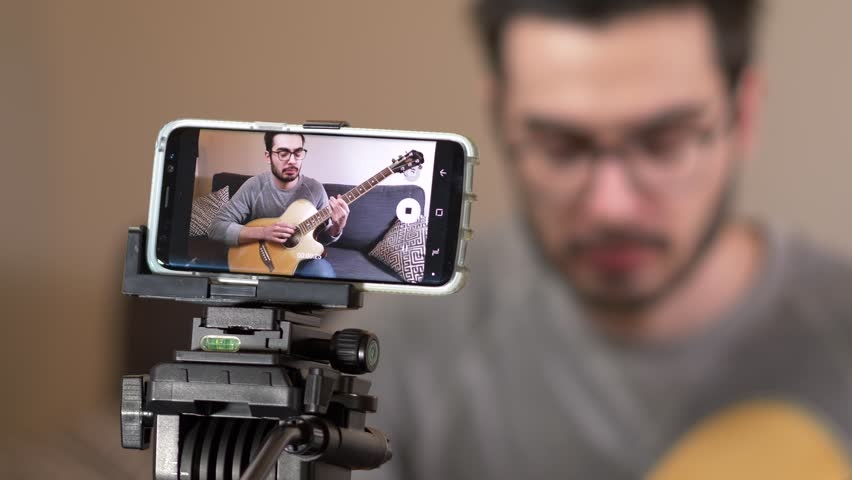 Musician vlogger recording a video of himself to post it on social media to be viewed by many viewers. | Shutterstock HD Video #1028200403