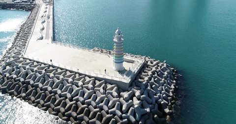 Aerial view of a breakwater and a lighthouse on the sea in Busan, South Korea