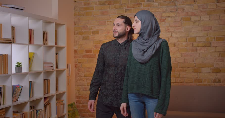 Closeup shoot of young attractive arabian couple settling in a newly bought apartment indoors | Shutterstock HD Video #1028203673
