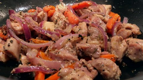 Juicy chopped chicken is fried in a pan with vegetables and spices. A typical meal for a low-carb diet