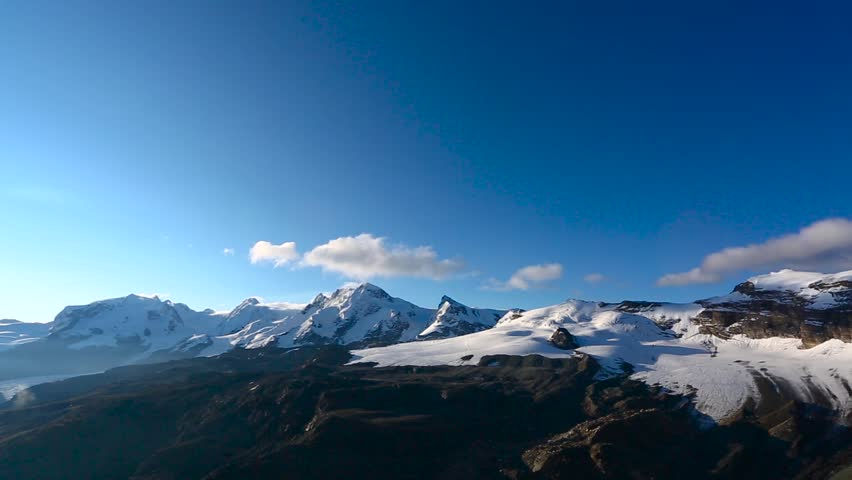 Panoramic footage of North east view of the Matterhorn peak and area during sunrise in sunny day with deep blue sky. Matterhorn (peak Cervino) in Swiss Alps. Beautiful natural landscape in the | Shutterstock HD Video #1028210033