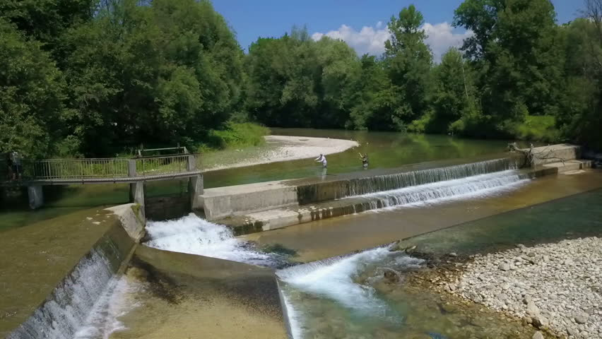 A dam was built on this river and we can see it in the front of the video. There are two fishermen fishing in the back. It's a hot summer day. Aerial shot.